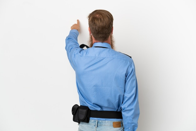 집게 손가락으로 다시 가리키는 흰색 배경에 고립 된 빨간 머리 경찰 남자