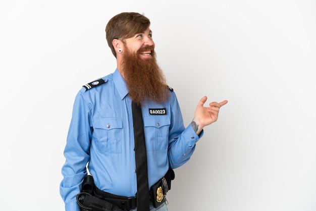 Рыжий полицейский, изолированные на белом фоне, указывая пальцем в сторону и представляя продукт