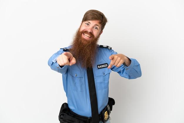 흰색 배경에 고립 된 빨간 머리 경찰 남자는 웃는 동안 당신에게 손가락을 가리 킵니다