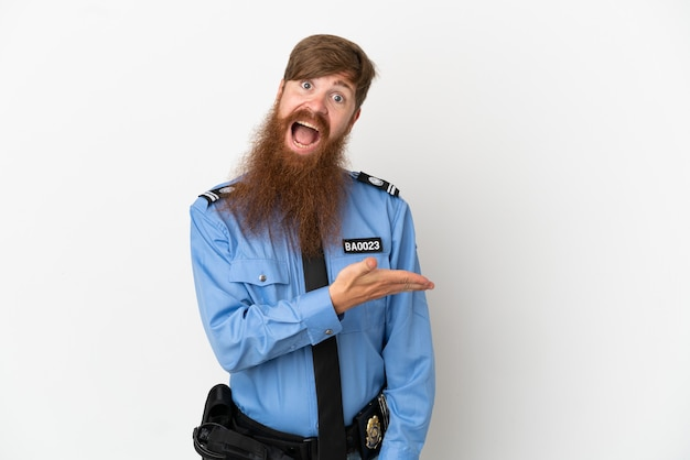 흰색 배경에 격리된 빨간 머리 경찰 남자는 웃고 있는 동안 아이디어를 제시합니다.