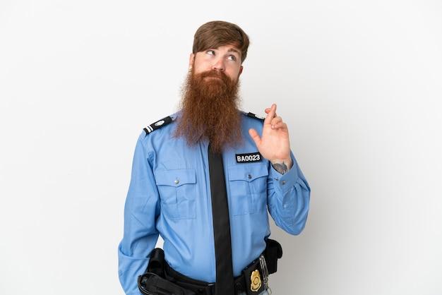 Рыжий полицейский изолирован на белом фоне со скрещенными пальцами и желает всего наилучшего