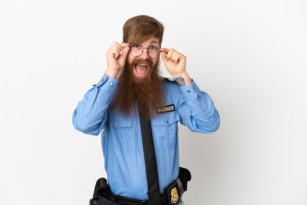 흰색 배경에 안경을 쓰고 놀란 빨간 머리 경찰 남자