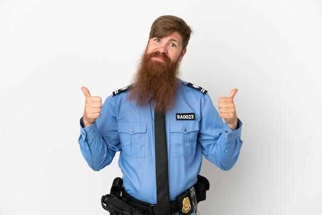 제스처와 미소를 엄지손가락으로 흰색 배경에 고립 된 빨간 머리 경찰 남자