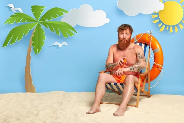 자외선 차단제와 함께 해변에서 포즈를 취하는 빨간 머리