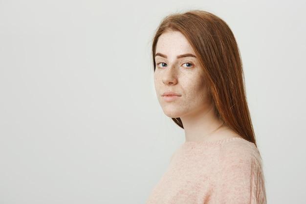 赤毛のかわいい女の子はカメラに顔を向け、深刻な探して