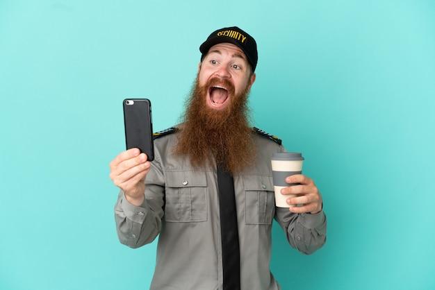 Рыжий охранник, изолированные на белом фоне, держит кофе на вынос и мобильный
