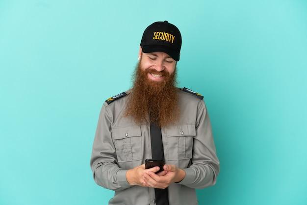 モバイルでメッセージを送信する白い背景で隔離赤毛の警備員