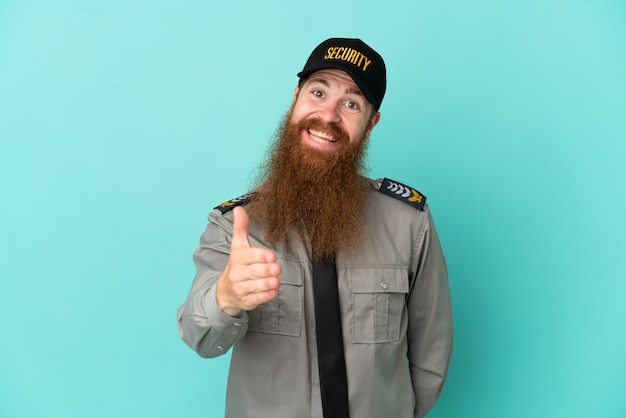 Redhead security man isolated on white background shaking hands for closing a good deal