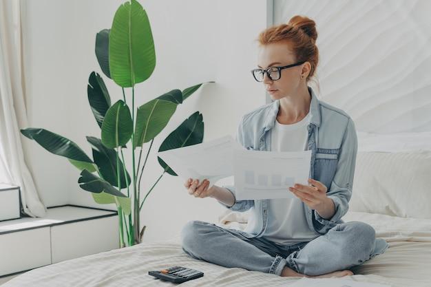 Рыжая серьезная кавказская женщина сидит в позе лотоса на кровати, изучает документы, подсчитывает счета