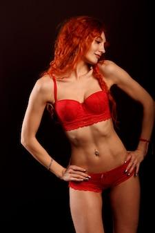 어두운 벽에 란제리의 빨간 머리 섹시한 카바레 댄서, 텍스트의 여유 공간