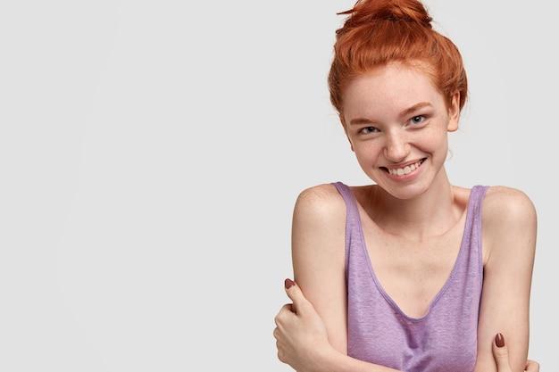 주근깨가있는 피부를 가진 빨간 머리 수줍은 여성, 부드러운 미소, 가슴 위로 손을 교차 유지, 친절한 표정으로 보임, 좋은 친근한 대화, 흰 벽에 서서, 여유 공간