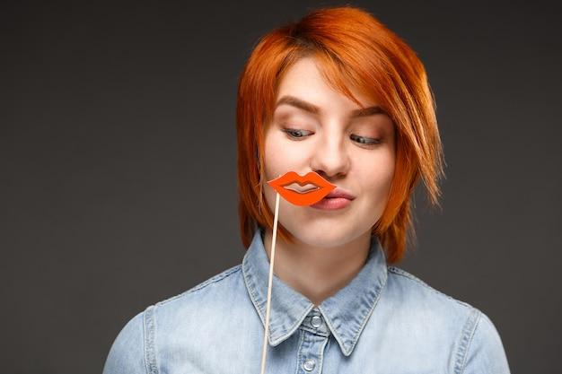 Рыжая глупая женщина держит поддельные губы и улыбается