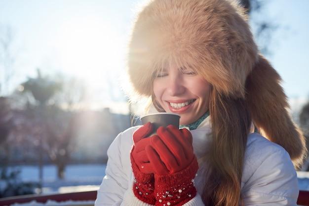 Рыжая тощая девушка, одетая в меховую шапку из лисы и белую куртку, пьет кофе, чтобы пойти зимой холодным днем и смеется.