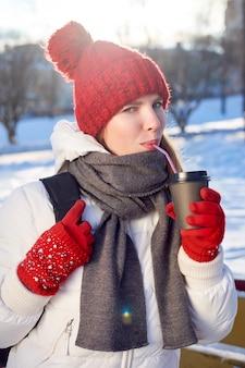 Рыжая худенькая студентка в красной вязаной шапке и белой куртке пьет кофе с собой в зимний холодный день