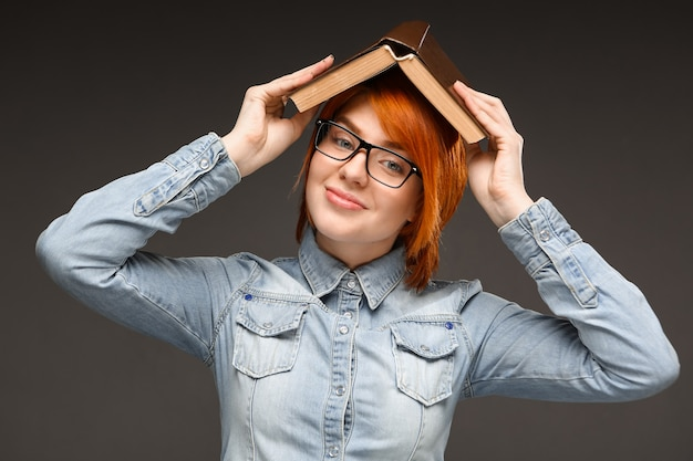 Redhead smiling woman studying, hold book on head