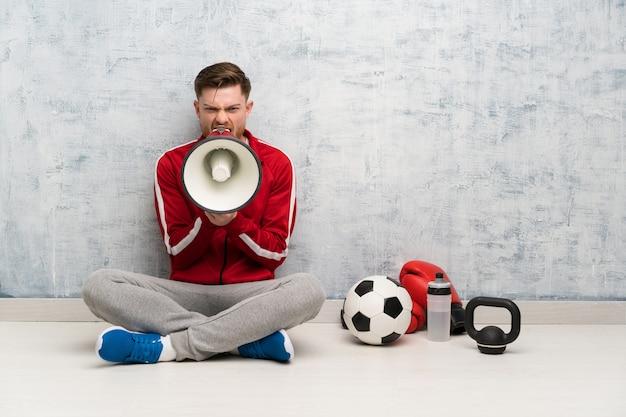 Redhead sport man shouting through a megaphone