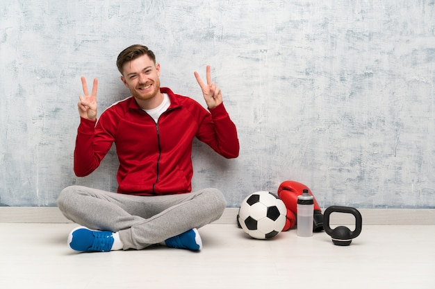 Redhead sport man showing victory sign with both hands