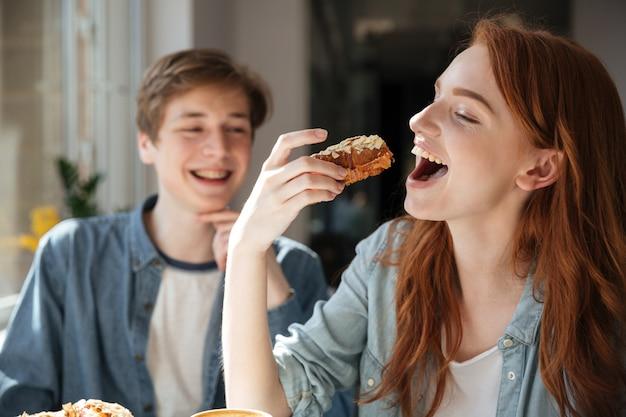 Рыжая студентка ест десерт