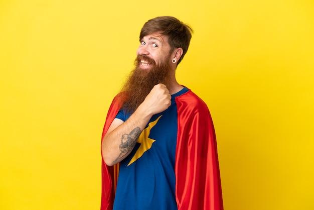 Рыжий человек супергероя изолирован на желтом фоне празднует победу