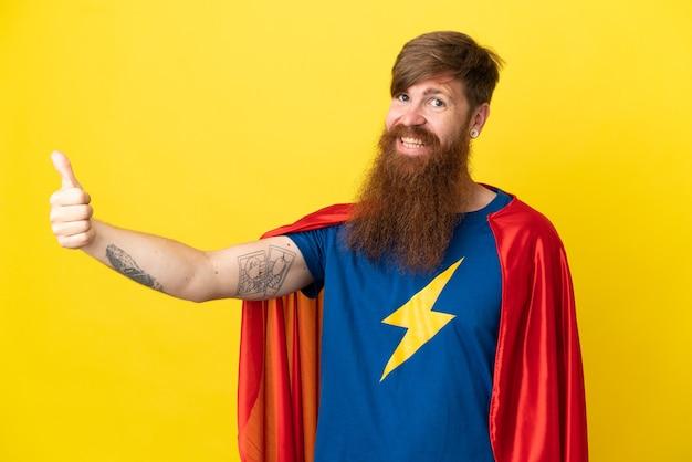빨간 머리 슈퍼 영웅 남자는 제스처를 엄지손가락을 포기 하는 노란색 배경에 고립