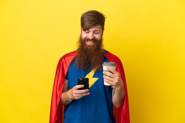 Рыжий супергерой, изолированный на желтом фоне, держит кофе на вынос и мобильный