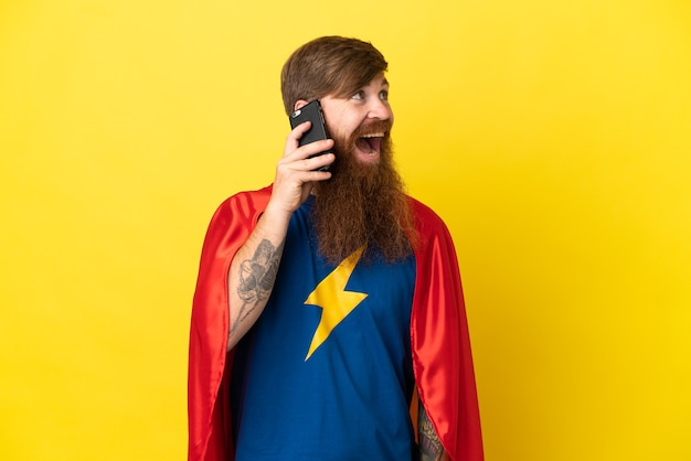 携帯電話との会話を維持している黄色の背景に分離された赤毛のスーパーヒーローの男