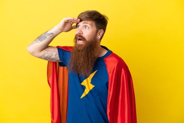 Рыжий супергерой мужчина изолирован на желтом фоне, глядя вдаль рукой, чтобы что-то посмотреть