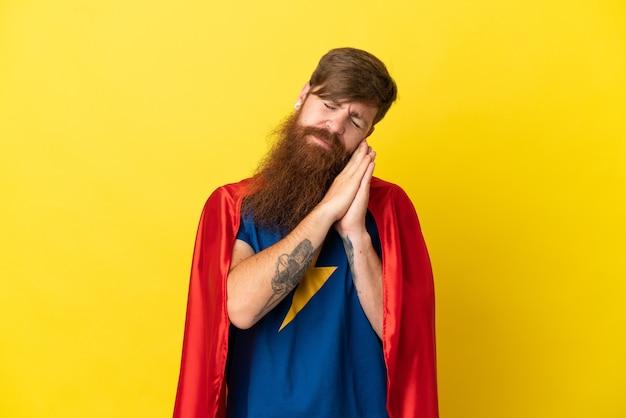 愛らしい表情で睡眠ジェスチャーを作る黄色の背景に分離された赤毛のスーパーヒーローの男