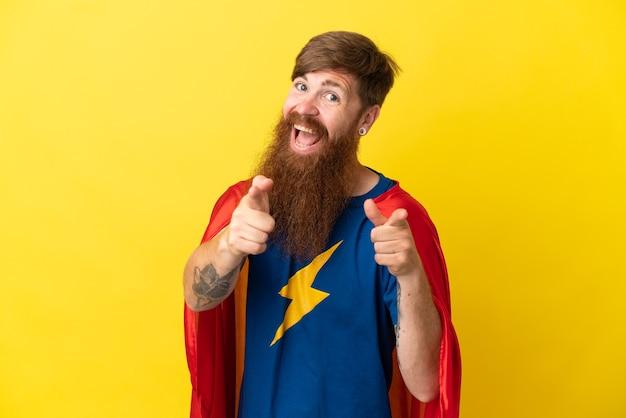 노란색 배경에 격리된 빨간 머리 슈퍼 히어로 남자는 정면을 가리키며 웃고 있습니다.