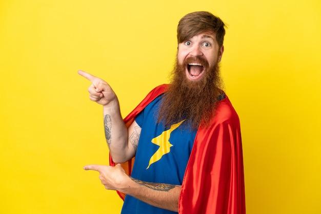 노란색 배경에 고립 된 빨간 머리 슈퍼 영웅 남자 놀라고 가리키는 측면