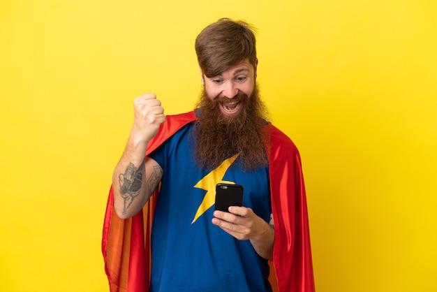 黄色の背景に孤立した赤毛のスーパーヒーローの男は驚いてメッセージを送信します