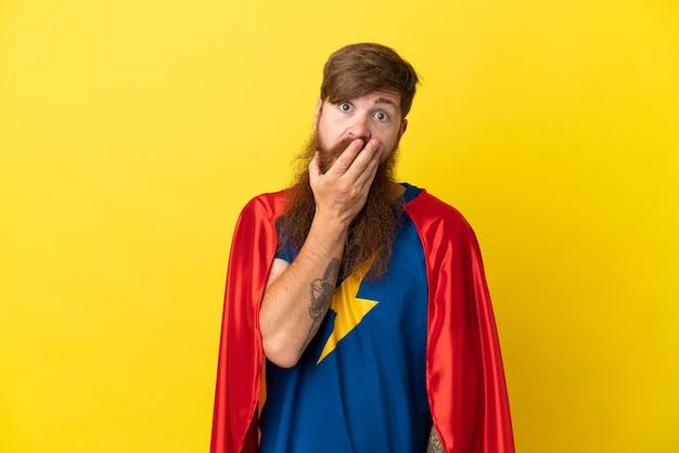 黄色の背景に孤立した赤毛のスーパーヒーローの男は、右を見ながら驚いてショックを受けました
