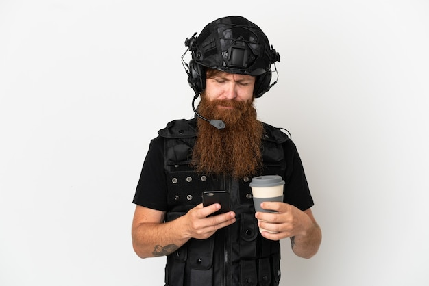 Рыжий спецназ, изолированные на белом фоне, держит кофе на вынос и мобильный