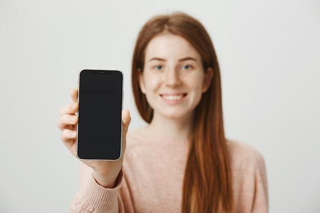 Ragazza adolescente rossa che mostra il display dello smartphone