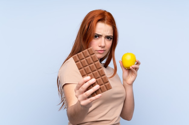 Redhead teenager girl over blue taking a chocolate tablet in one hand and an apple in the other