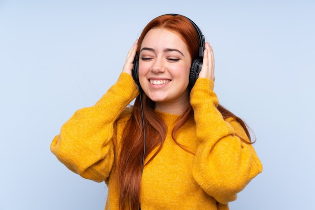 Redhead teenager girl over isolated blue wall listening music