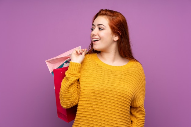 Redhead teenager girl over isolated purple wall holding shopping bags and looking back