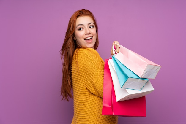 Redhead teenager girl over isolated purple wall holding shopping bags and smiling
