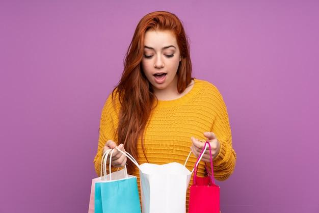 격리 된 보라색 벽 쇼핑백을 들고 그 안에 찾고 빨간 머리 십 대 소녀