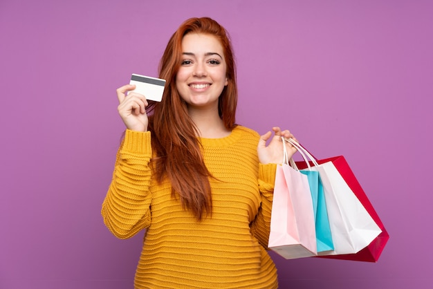 Redhead teenager girl over purple holding shopping bags and a credit card