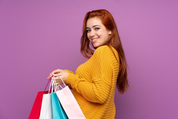 Redhead teenager girl over purple holding shopping bags and smiling