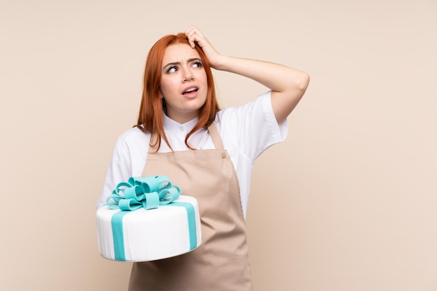 Redhead teenager girl with a big cake over isolated wall having doubts and with confuse face expression