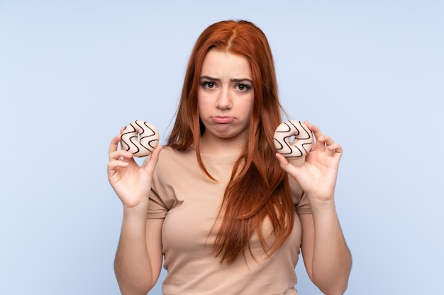 Redhead teenager woman holding donuts with sad expression