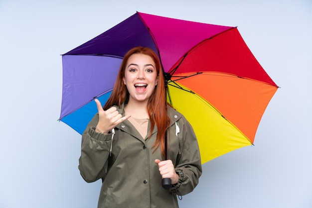 Redhead teenager woman holding an umbrella making phone gesture