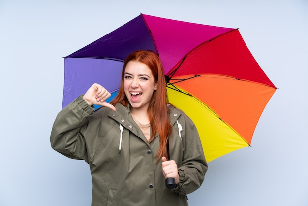 Redhead teenager woman holding an umbrella proud and self-satisfied
