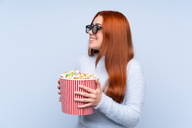 Redhead teenager woman over isolated blue wall with 3d glasses and holding a big bucket of popcorns