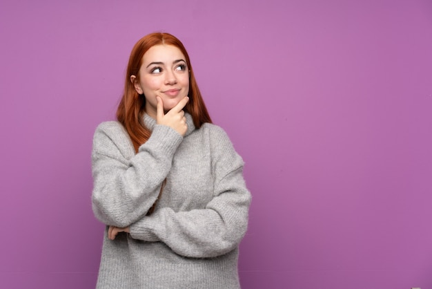 Redhead teenager woman over isolated purple wall thinking an idea