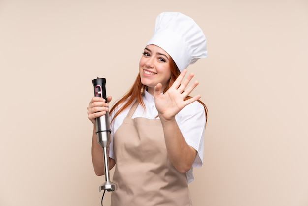 Redhead teenager woman using hand blender saluting with hand with happy expression