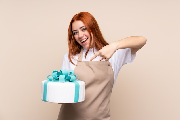 Redhead teenager woman with a big cake and pointing it