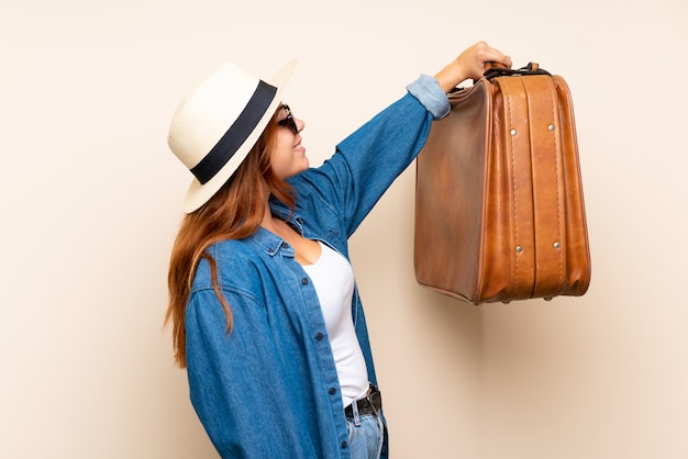 Redhead traveler girl with suitcase over isolated  with happy expression